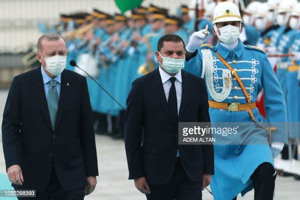 Turkish President Recep Tayyip Erdogan and Libyan government of national unity prime minister Abdul Hamid Dbeibah walk past honour guards during the...