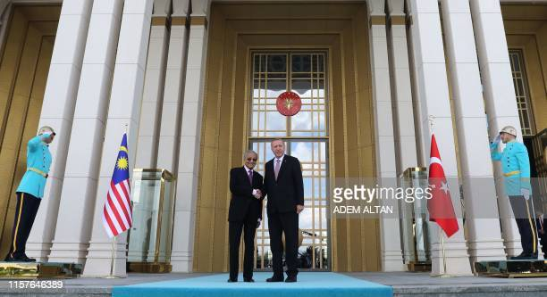 Turkish President Recep Tayyip Erdogan and Malaysian Prime Minister Mahathir Mohamad shake hands during an official welcoming ceremony at...