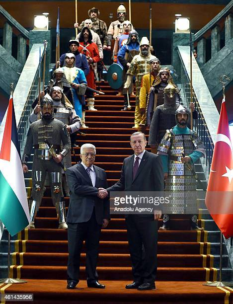Turkish President Recep Tayyip Erdogan and Palestinian President Mahmoud Abbas shake hands in front of the 16 soldiers who represent the 16 Turkish...