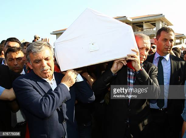 Turkish President Recep Tayyip Erdogan and Turkey's former President Abdullah Gul carry a coffin during the funeral ceremony of his campaign manager...