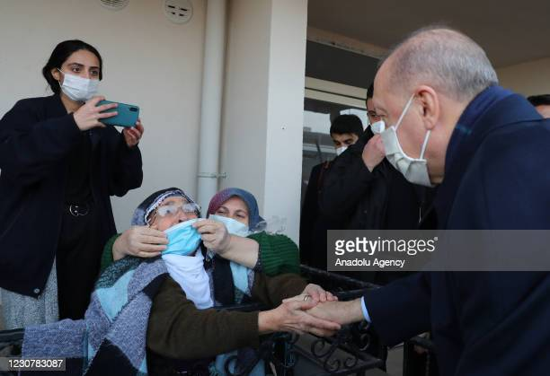 Turkish President Recep Tayyip Erdogan chats with citizens as he attends the ceremony to mark first anniversary of Elazig earthquake and for delivery...