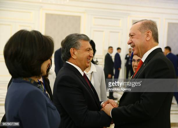 Turkish President Recep Tayyip Erdogan chats with Uzbekistani President Shavkat Mirziyoyev after the welcoming ceremony during his official visit in...