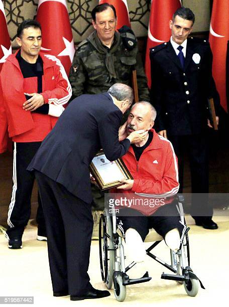 Turkish President Recep Tayyip Erdogan delivers a plaque to police officers Omer Kula who lost his legs during an antiterror operation at a ceremony...