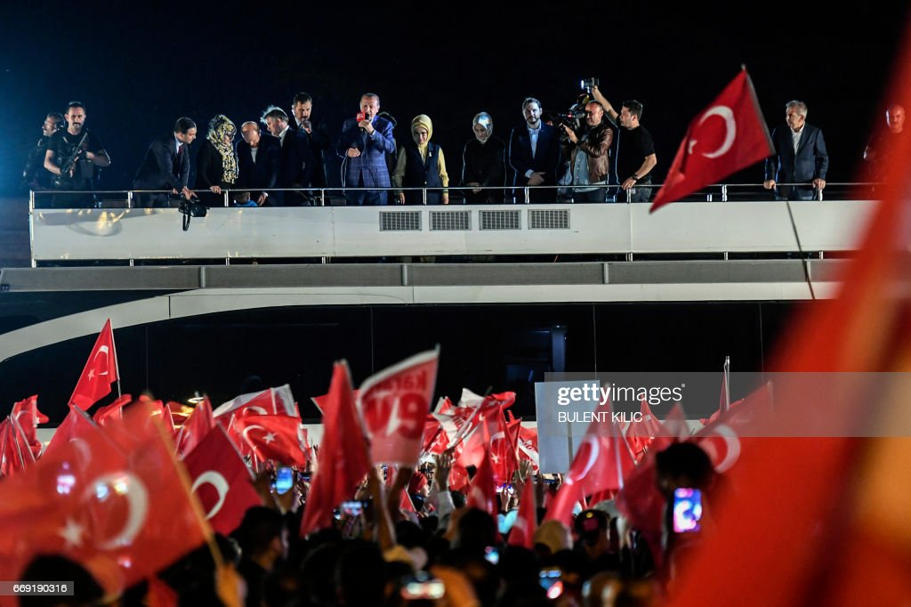 Turkish president Recep Tayyip Erdogan (C) delivers a speech to supporters in Istanbul, on April 16, 2017, after the results of a nationwide referendum that will determine Turkey's future destiny. Erdogan on April 16, 2017 hailed Turkey for making a 'historic decision' as he claimed victory in the referendum on a new constitution expanding his powers. The 'Yes' campaign to give Turkish President expanded powers won with 51.3 percent of the vote a tightly-contested referendum although the 'No' camp had closed the gap, according to initial results. But Turkey's two main opposition parties said they would challenge the results. /
