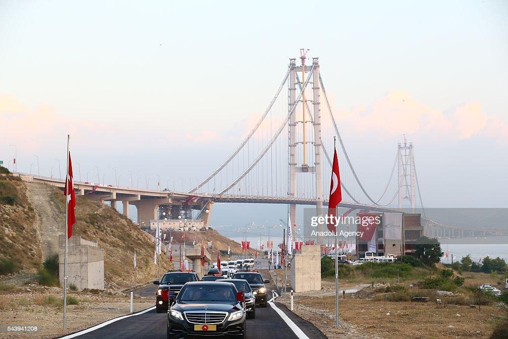 Turkish President Recep Tayyip Erdogan drives across the bridge with Turkish Prime Minister Binali Yildirim during the opening ceremony of Osmangazi Bridge in Kocaeli, Turkey on June 30, 2016. Osmangazi Bridge is the fourth-longest suspension bridge in the world and second-longest bridge in Europe.