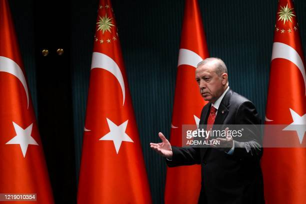 Turkish President Recep Tayyip Erdogan gestures and reacts as he arrives on stage to deliver a speech following a cabinet meeting in Ankara on June 9...