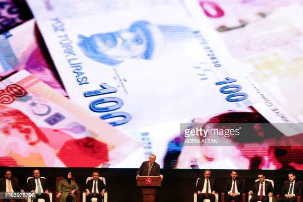 Turkish President Recep Tayyip Erdogan gestures as he delivers a speech on stage, with on the background banknotes of the Turkish Lira, during the...