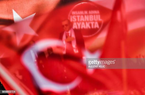 Turkish President Recep Tayyip Erdogan gestures as he stands behind a national flag during a protest rally in Istanbul on May 18 against the recent...