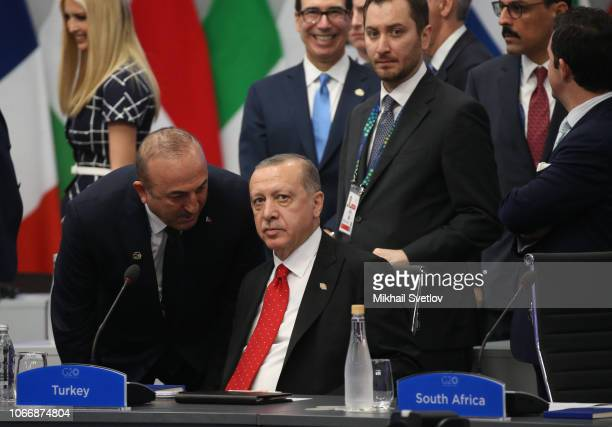 Turkish President Recep Tayyip Erdogan listens to Foreign Minister Mevlut Cavusoglu during the G20 Summit's Plenary Meeting on November 30 2018 in...
