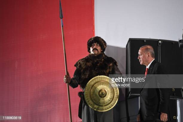 Turkish president Recep Tayyip Erdogan passes next to a Turkish soldier wearing a ottoman uniform during a third anniversary commemoration rally at...