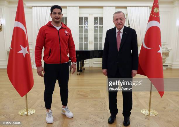 Turkish President Recep Tayyip Erdogan poses for a photo with Turkish wrestlers Taha Akgul during his iftar dinner with national athletes who won...