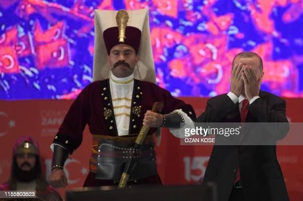 Turkish president Recep Tayyip Erdogan prays next to a Turkish soldier wearing a ottoman uniform during a third anniversary commemoration rally at...