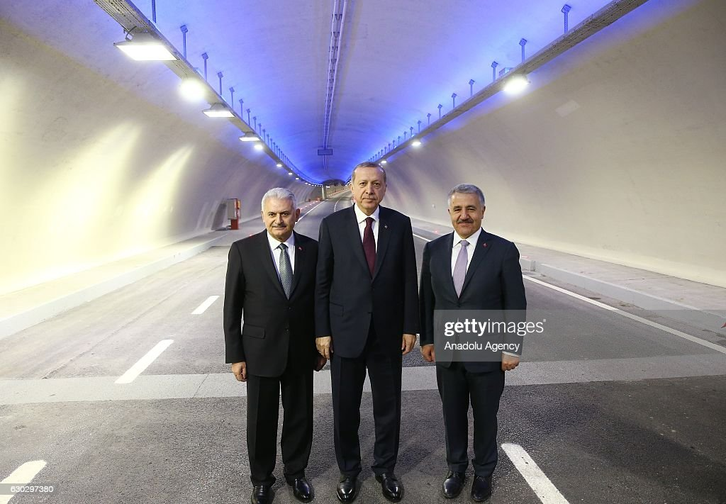 Turkish President Recep Tayyip Erdogan (C), Prime Minister of Turkey Binali Yildirim (L) and Turkish Minister of Transport, Maritime and Communication Ahmet Arslan (R) pose for a photo on the road as they were passing through the Eurasia Tunnel, connecting Asian and European sides under the Bosporus, with a convoy after its opening ceremony in Istanbul, Turkey on December 20, 2016. The Eurasia Tunnel was constructed underneath the seabed of the Bosphorus by ATAS, a company whose shares are equally owned by prominent Turkish contractor Yapi Merkezi and a major international company -- SK E&C from South Korea. Construction of the two-story undersea tunnel took over four years. The total length of the project is 14.6 kilometers (nine miles) and the most crucial part, the Bosphorus crossing, is 5.4km long.