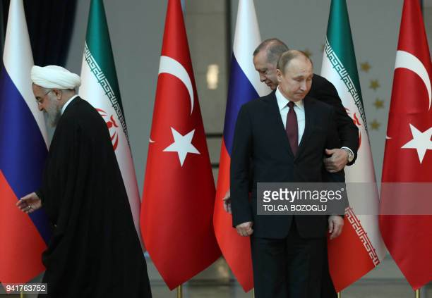 Turkish President Recep Tayyip Erdogan Russian President Vladimir Putin and President of Iran Hassan Rouhani leave after a photo ahead of the...