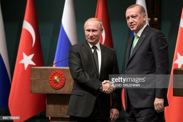 Turkish President Recep Tayyip Erdogan shake hands with Russian President Vladimir Putin after their joint press conference at the Presidential...