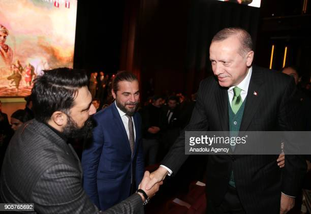 Turkish President Recep Tayyip Erdogan shakes hands with a participant as he is flanked by actor Engin Altan Duzyatan during the premiere of the...