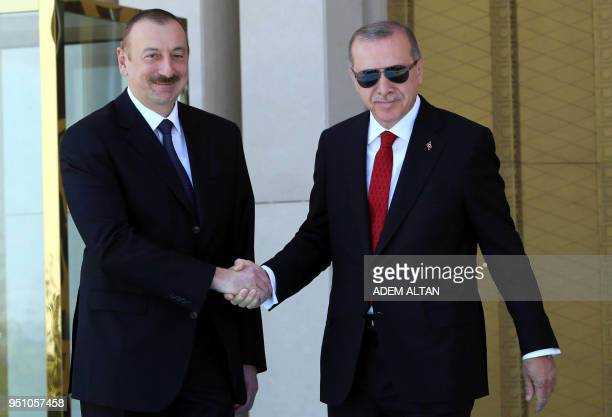 Turkish president Recep Tayyip Erdogan shakes hands with Azerbaijan's President Ilham Aliyev during an official welcome ceremony at the Presidential...