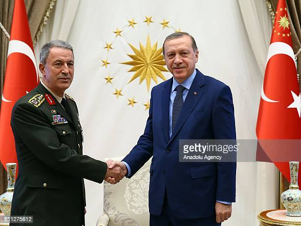 Turkish President Recep Tayyip Erdogan shakes hands with Chief of the General Staff of Turkey Hulusi Akar at the Presidential Complex in Ankara...