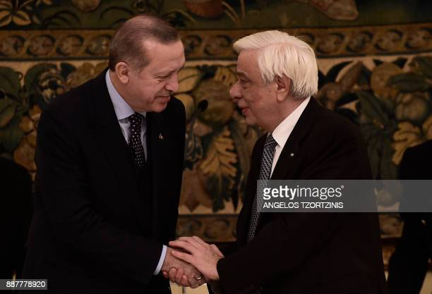 Turkish President Recep Tayyip Erdogan shakes hands with Greece's President Prokopis Pavlopoulos at an official dinner in Athens on December 7 during...
