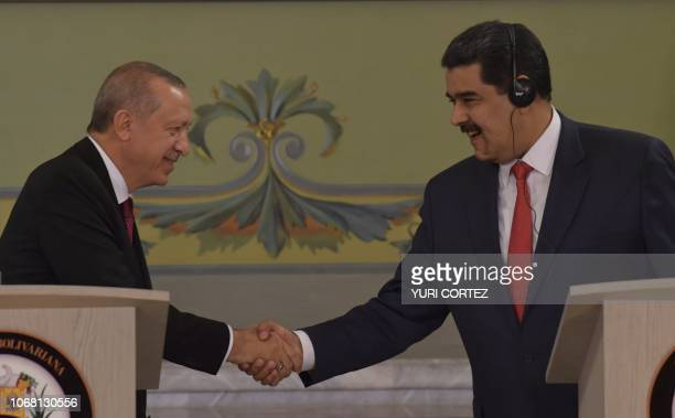 Turkish President Recep Tayyip Erdogan shakes hands with his Venezuelan counterpart Nicolas Maduro after a joint press conference at Miraflores...
