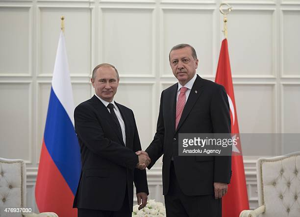Turkish President Recep Tayyip Erdogan shakes hands with Russian President Vladimir Putin in Baku where he attended the opening ceremony of the First...