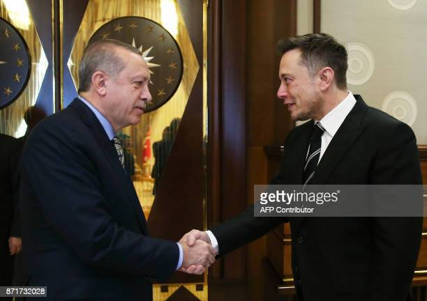 Turkish President Recep Tayyip Erdogan shakes hands with the founder of US aerospace manufacturer and space transport services company SpaceX Elon...