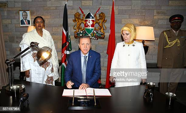 Turkish President Recep Tayyip Erdogan signs the guest book as his wife Emine Erdogan and Kenyan Foreign Minister Amina Mohamed stand near him at the...