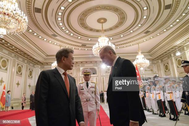 Turkish President Recep Tayyip Erdogan walks with South Korean President Moon Jae-in as they review an honour guard during a welcoming ceremony at...