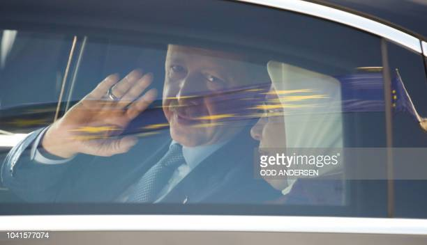 Turkish President Recep Tayyip Erdogan waves as he sits inside a car with his wife Emine Erdogan as a European flag is reflected on the car window...