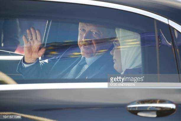 TOPSHOT Turkish President Recep Tayyip Erdogan waves as he sits inside a car with his wife Emine Erdogan as a European flag is reflected on the car...