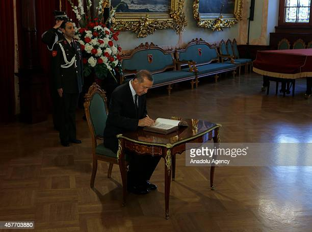Turkish President Recep Tayyip Erdogan writes in the visitor's book ahead of a meeting at House of the Blackheads in Riga Latvia on October 23 2014