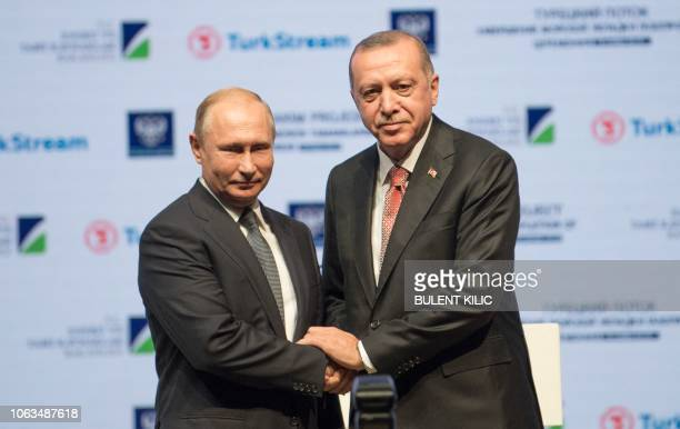 Turkish President Tayyip Erdogan and his Russian counterpart Vladimir Putin shake hands on stage during a ceremony to mark the completion of the sea...