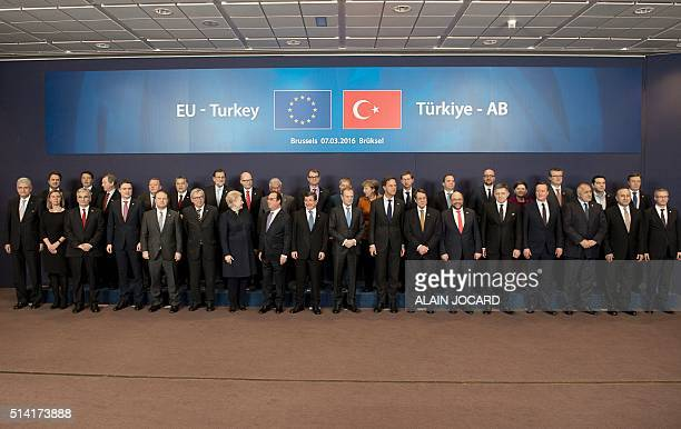 Turkish Prime Minister Ahmet Davutoglu and European Council president Donald Tusk pose for a family picture with European leaders during an EU...