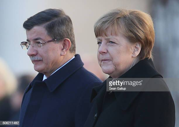 Turkish Prime Minister Ahmet Davutoglu and German Chancellor Angela Merkel listen to their countries' respective national anthems following...