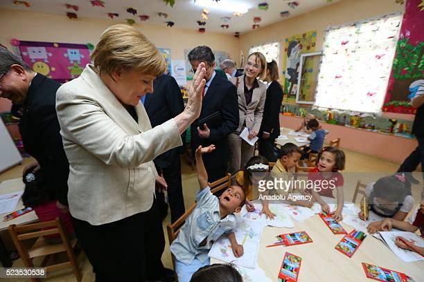 Turkish Prime Minister Ahmet Davutoglu and German Chancellor Angela Merkel visit refugees at Nizip container city in Gaziantep Turkey on April 23 2016