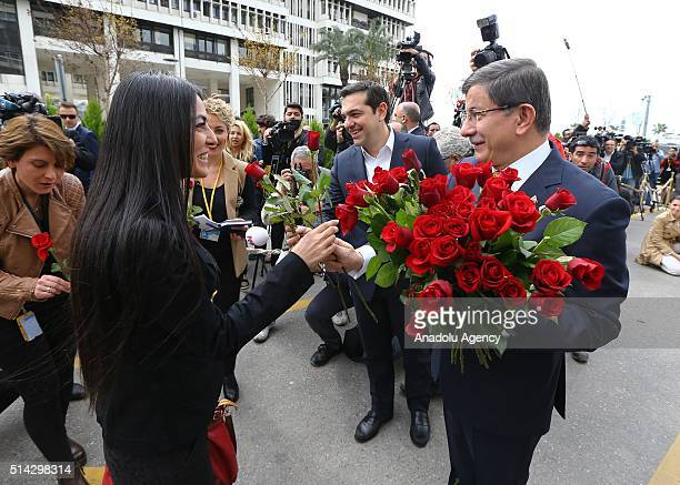 Turkish Prime Minister Ahmet Davutoglu and Greek Prime Minister Alexis Tsipras give red roses to the female journalists to mark International Women's...