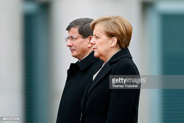 Turkish Prime Minister Ahmet Davutoglu chats with German Chancellor Angela Merkel during a military honor ceremony upon Davutoglu's arrival for talks...