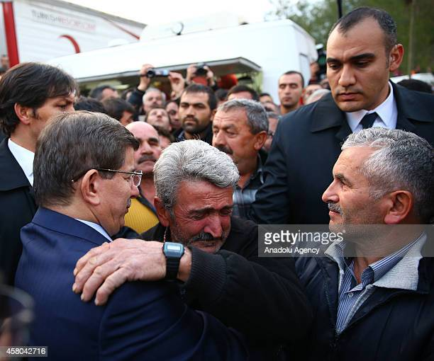 Turkish Prime Minister Ahmet Davutoglu consoles the relatives of trapped miners as search and rescue teams work to rescue 18 remaining trapped miners...