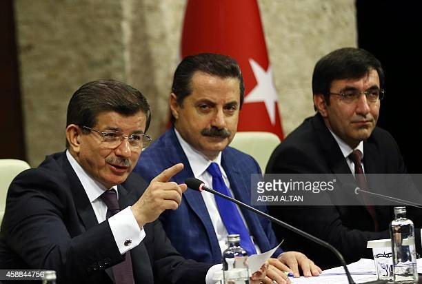 Turkish Prime Minister Ahmet Davutoglu gestures during a press briefing at the Prime Ministry Office in Ankara on November 12 flanked by Minister of...