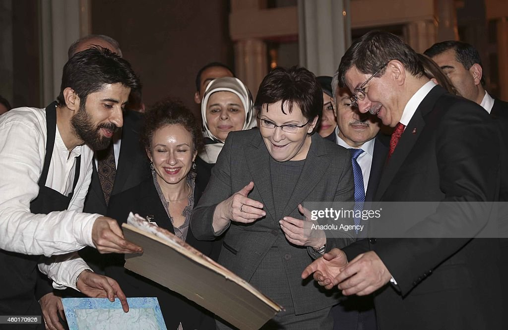 Turkish Prime Minister Ahmet Davutoglu (R) gives a paper marbling on which there are Turkish and Polish flags, made by the marbling artist Garip Ay (L) during the concert, to Polish Prime Minister Ewa Kopacz (R 2) at the closing ceremony of the celebrations marking the 600th anniversary of the establishment of diplomatic relations between Turkey and Poland at the Grand Theatre (Teatr Wielki) in Warsaw, Poland on December 08, 2014.