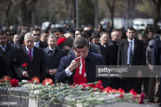 Turkish Prime Minister Ahmet Davutoglu puts a Turkish flag to the place where the Ankara terror attack took place in Ankara Turkey on March 17 2016