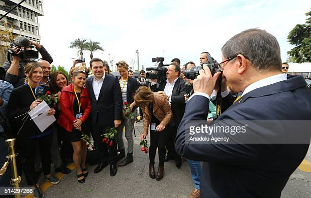 Turkish Prime Minister Ahmet Davutoglu takes photos of journalists and his Greek counterpart Alexis Tsipras as they give red roses to the female...