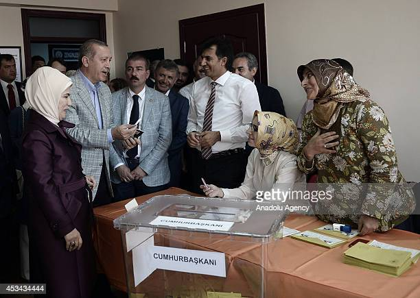 Turkish Prime Minister and Presidential candidate Recep Tayyip Erdogan gives his badge to the polling clerk Meltem Gencturk as a remembrance after...