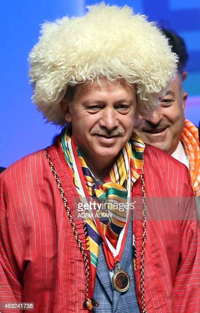 Turkish Prime Minister and presidential candidate Recep Tayyip Erdogan poses wearing a Turkmen hat during a meeting of his ruling Justice and...