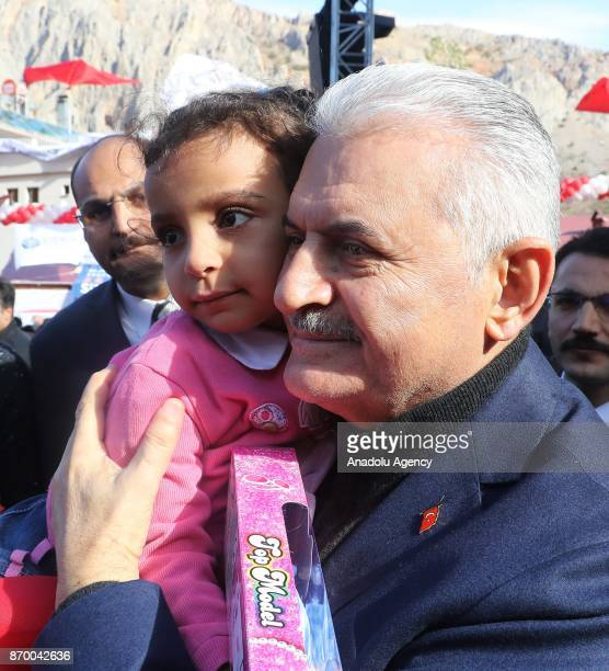 Turkish Prime Minister Binali Yildirim poses for a photo with a girl during groundbreaking ceremony for new road Kemaliye Dutluca on November 4 2017...