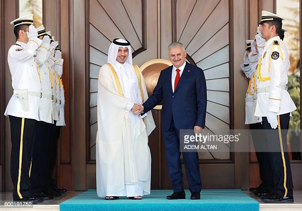Turkish Prime Minister Binali Yildirim shakes hands with Qatar's Prime Minister Abdullah bin Nasser bin Khalifa Al Thani before their meeting at...
