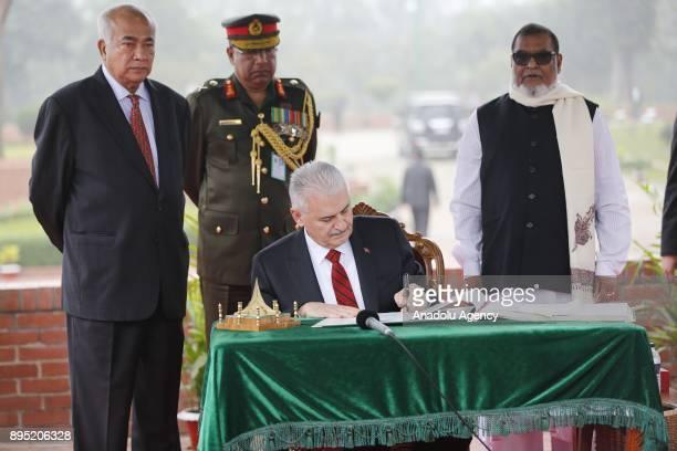 Turkish Prime Minister Binali Yildirim signs the guest book as he visits the National Martyrs' Memorial at Savar Dhaka Bangladesh on December 19 2017