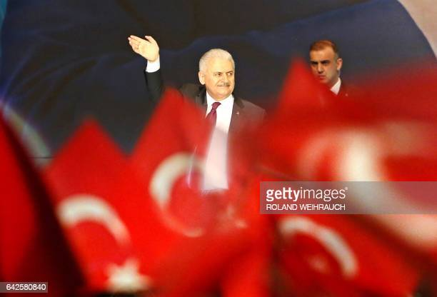 Turkish Prime Minister Binali Yildirim waves after delivering a speech during an event in Oberhausen western Germany on February 18 2017 to promote...