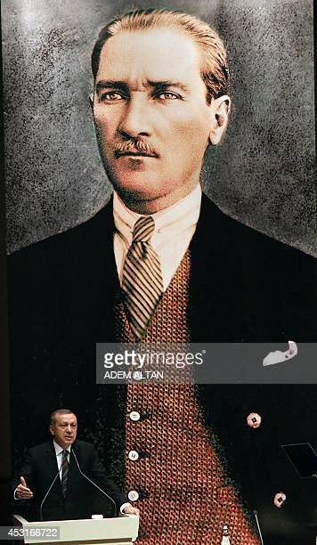 Turkish Prime Minister Recep Tayyip Erdogan delivers a speech with behind him a giant portrait of the Republic's founder Mustafa Kemal Ataturk on...