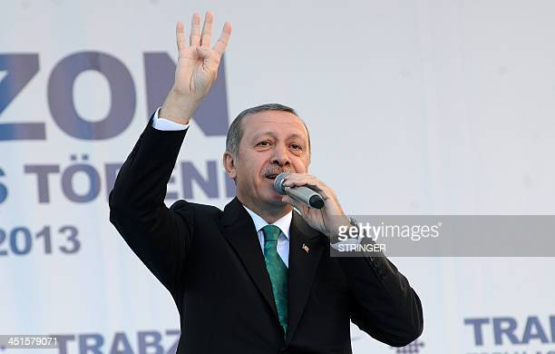 Turkish Prime Minister Recep Tayyip Erdogan gestures the fourfinger salute used by supporters of ousted Egyptian president Mohamed Morsi a symbol...